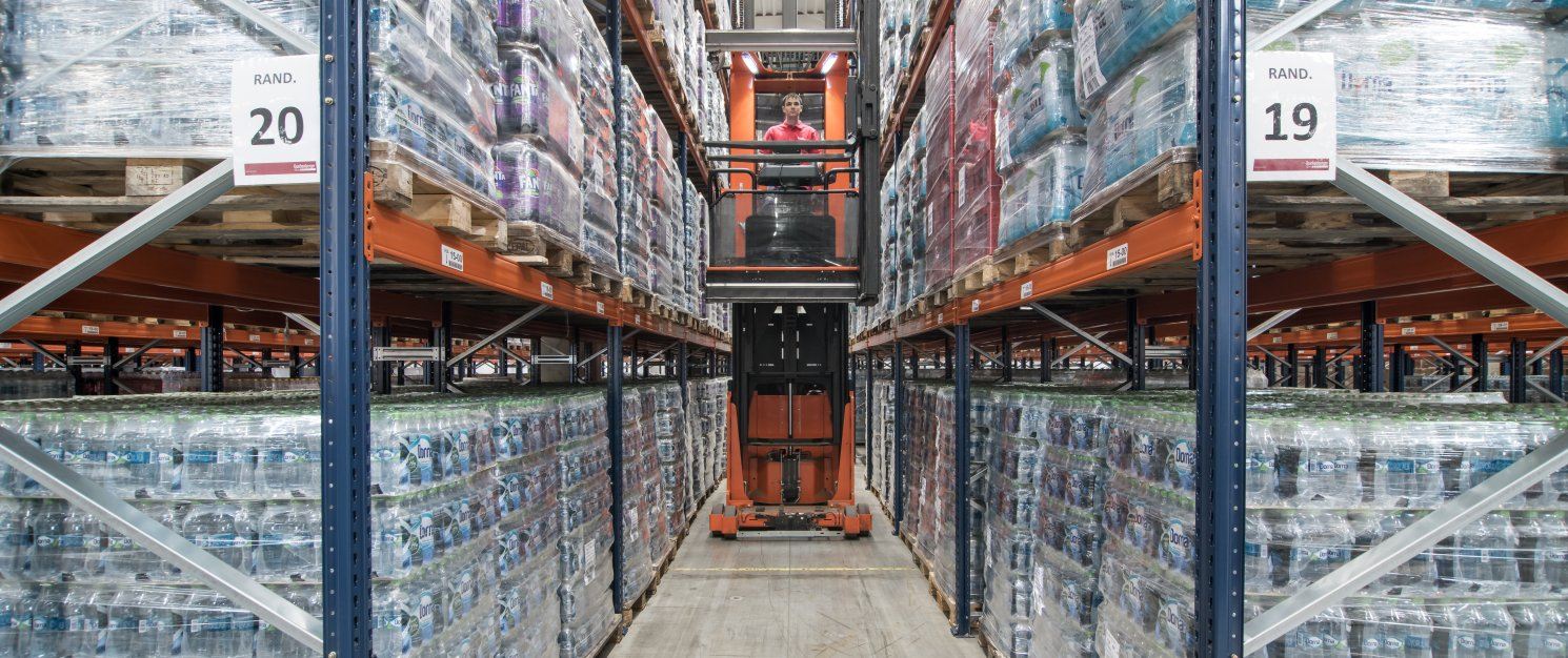 Forklift drives through a warehouse aisle with filled high-rack storage shelves.