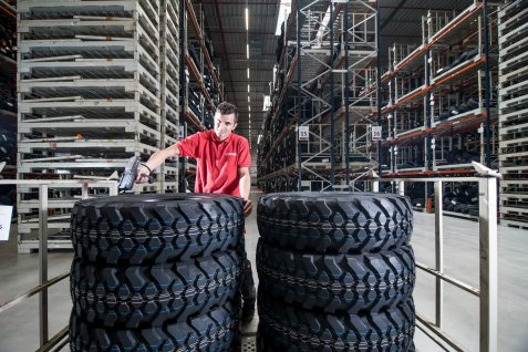 Employee works in a warehouse with a tower of stacked tyres.