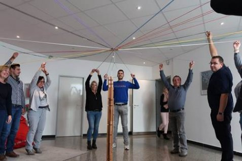 Group of employees standing in a circle around a stick with strings attached to it.