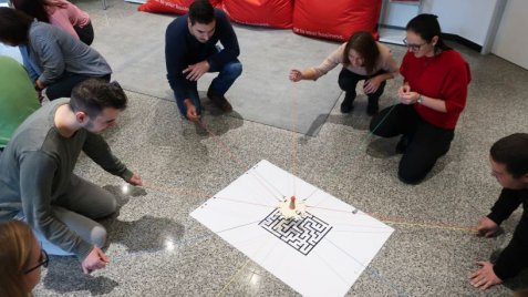 A group of employees kneeling around a poster with a labyrinth on it through which they try to move a game token with the help of strings.