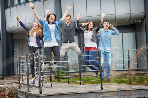 Group of employees enthusiastically jumping up into the air in front of a building.