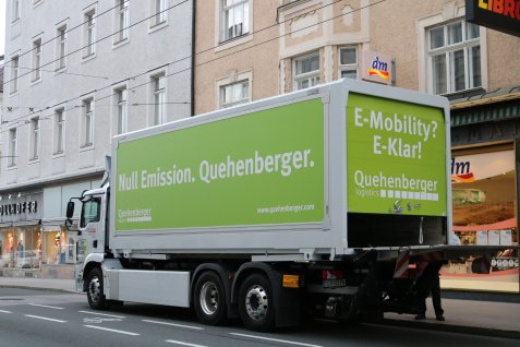 Quehenberger e-truck in front of a chemist's chain store.