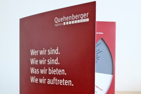 The brand steering wheel of Quehenberger standing opened on a table.